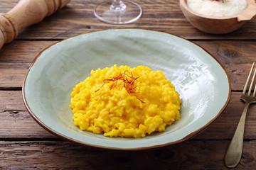 risotto allo zafferano tradizionale italiano su sfondo tavolo di cucina rustico