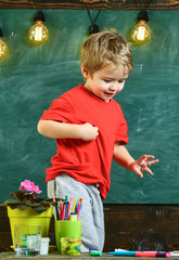 Boy standing behind the table with potted flowers, markets and pencils. Cute, blond kid looking down.
