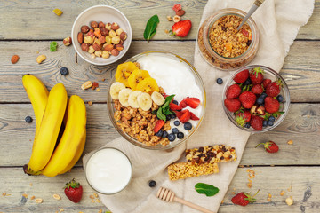 Bowl of homemade granola with yogurt and fresh berries on wooden background
