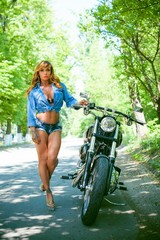 Biker concept. Bodybuilder mature sexy woman with a motorbike, lifestyle portrait of muscular woman, american middle age model