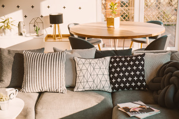 Black and white decorative pillows on a gray sofa in a sunlit living room interior with a wooden dining table