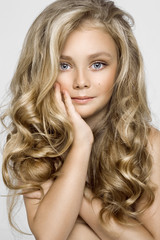 Portrait of a lovely little girl with long hair on a white background in the studio.