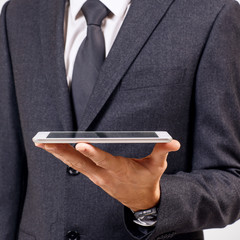 Businessman holds digital tablet. Close-up shot.