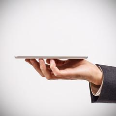 Businessman holds digital tablet against gray background.