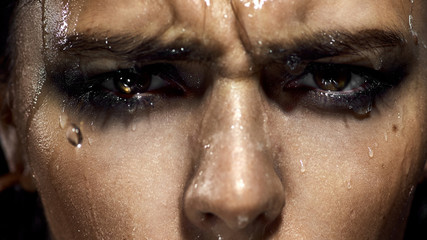 large portrait of the girl's face. Eyes, lips, makeup, crazy emotion. Water runs down the skin. The chain in his teeth.