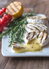 Grilled Camembert cheese with cherry tomatoes and rosemary