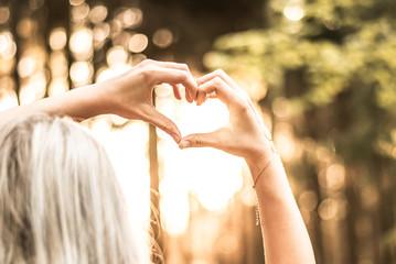 Frau formt ein Herz im Sonnenuntergang