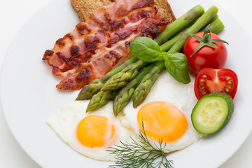 Fried eggs with bacon on the wooden table.