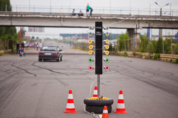 Traffic light at the start of a racing track with a car in the distance