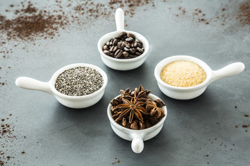 Coffee beans, seeds and star anise in small, matching bowls on a gray table. Concept of flavoring food