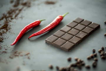 Close-up of hot, red peppers next to a bar of dark chocolate. Mixing flavors concept. Focus in the center and blurred edges,.