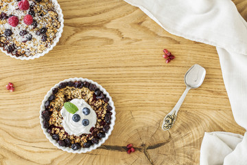 Top view of a wooden breakfast table with two bowls of oatmeal with fruit, elegant silver spoon and white cloth