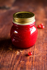 Jar of freshly made red currant jelly jam or sauce on a wooden table, selective focus. Image with copy space. Rustic style.