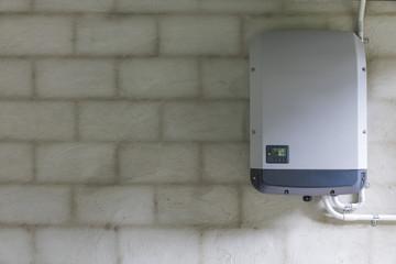 Solar power inverter mounted on brick wall inside garage