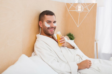 Recreational time. Positive happy man drinking orange juice while relaxing at home