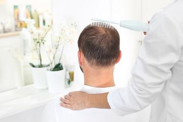 Mezoterapia tlenowa skóry głowy.  Głowa mężczyzny z przerzedzonymi włosami podczas zabiegu...