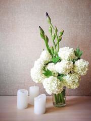 Белый букет и свечи на столе.
