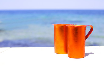 Two orange cups on sea background