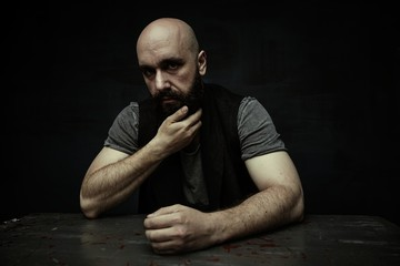 portrait of pensive young bearded man looking at camera