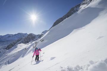 High angle of a woman climbing up the ski slope, Bavaria, Germany, Europe