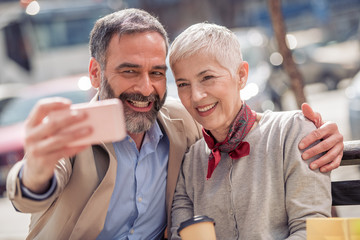 Happy mature couple taking a selfie in the city