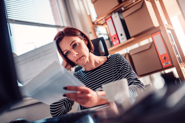 Worried woman reading mail at the office