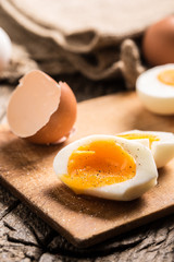 Close-up boiled or raw chicken eggs on wooden board