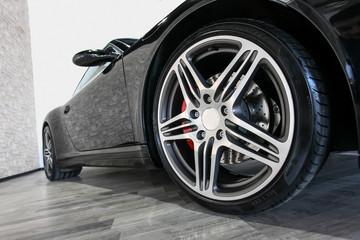 Black sport car on showroom floor with shiny wheel Fototapete