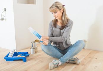 Fototapeta beautiful female worker designer sitting on the floor holding co