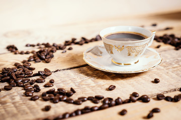 cup of delicious and fragrant coffee on a wooden old table with seeds