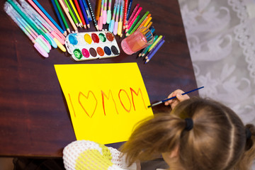 """Cute little kid girl writes the text """"I love mom"""" by marker. Concept of kids hobby or childhood, happy lifestyle"""