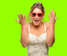 Young beautiful woman wearing red sunglasses happy and surprised cheering expressing wow gesture
