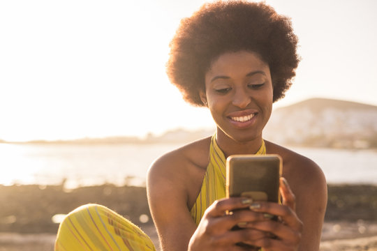 daily summer sunnny scene with black race afro american beautiful girl with alternative hair looking at the phone and check social media. sunny golden light beach and ocean in the background.