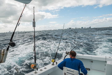 A man in a fishing boat in a stormy ocean with a view of the coast of Miami. fishing in Florida. USA.