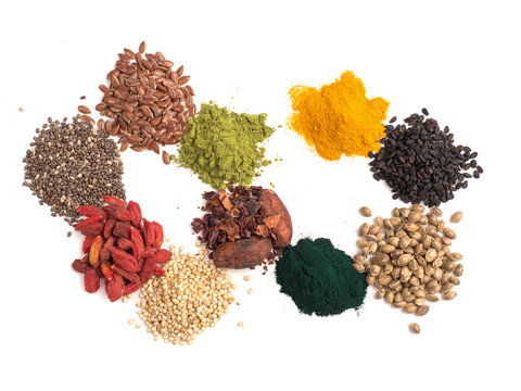 Small heap of various superfoods on white background.Superfood as chia,spirulina,matcha tea,raw cocoa bean,goji,hemp,quinoa,black sesame,turmeric,flax seed.Top view.Isolated on white,clipping path