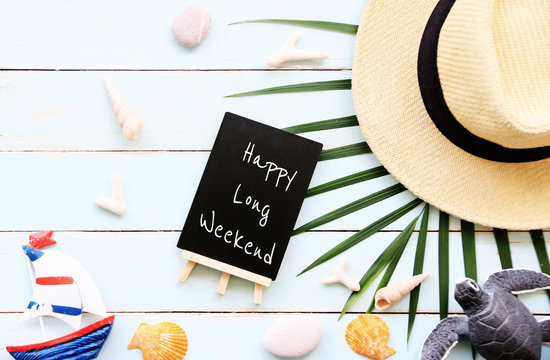 HAPPY LONG WEEKEND Text on blackboard with summer holiday background