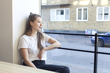 Young girl sitting in a café looking out the window