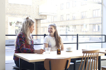 Two Scandinavian girls sitting in a café laughing and talking