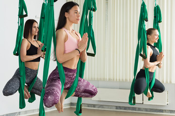 Young women performing yoga exercise in hammocks