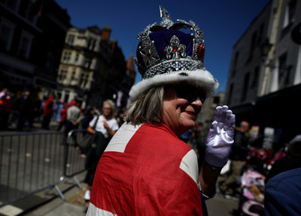 A fan of Britain's Royal Family wears a crown ahead of the wedding of Britain's Prince Harry and Meghan Markle in Windsor