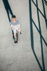 Boy skates on skateboard on asphalt road
