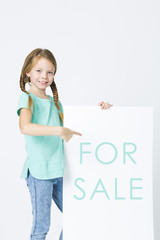 for sale - pretty, brunette girl is pointing at white board in front of white background