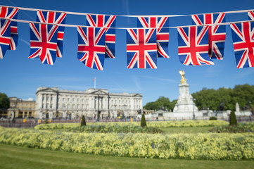 Union Jack flag bunting decorates The Mall in front of a park with spring flowers and Buckingham Palace ahead of Royal Wedding in London, England.