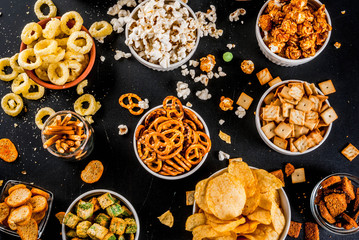 Variation different unhealthy snacks crackers, sweet salted popcorn, tortillas, nuts, straws, bretsels, back chalkboard copy space Fototapete