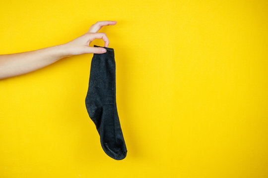 old smelly holey sock in hand on a yellow background