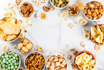 Variation different unhealthy snacks crackers, sweet salted popcorn, tortillas, nuts, straws, bretsels, white marble background copy space Fototapete