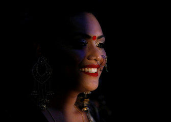 Light illuminates a performer during the Miss Pink Beauty Pageant in Kathmandu