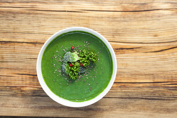 Spinach green soup with broccoli in white bowl on wooden background top view.