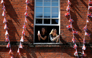 Women take photos on their smartphones as they lean out of the window of a building near Windsor Castle in Windsor