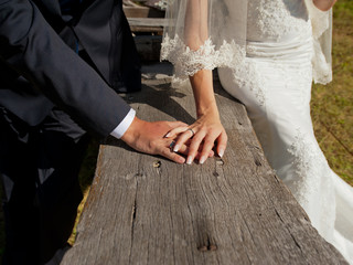 The bride and groom in wedding suits hold hands on the background of a wooden board. Close-up.